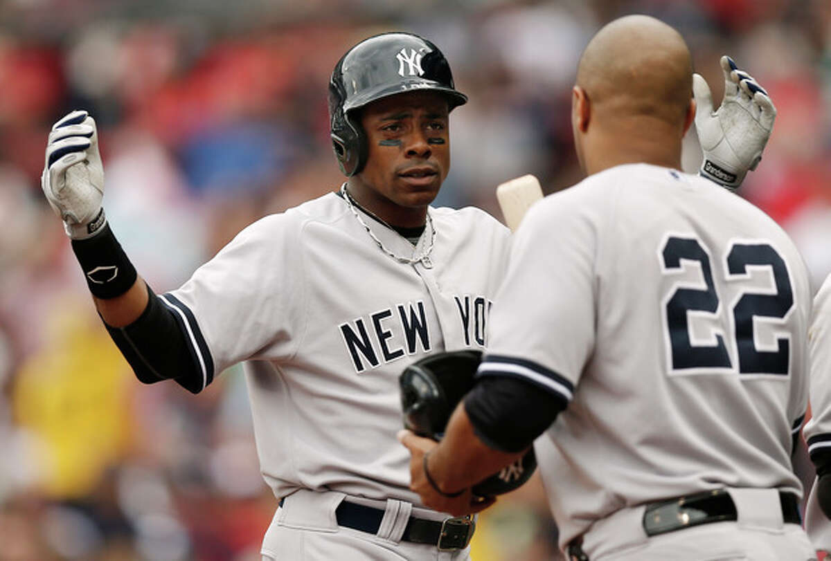 New York Yankees' Curtis Granderson gestures at teammate Vernon Wells (22) while heading for the dugout during the fourth inning of a baseball game at Fenway Park in Boston Saturday, Sept. 14, 2013. (AP Photo/Winslow Townson)
