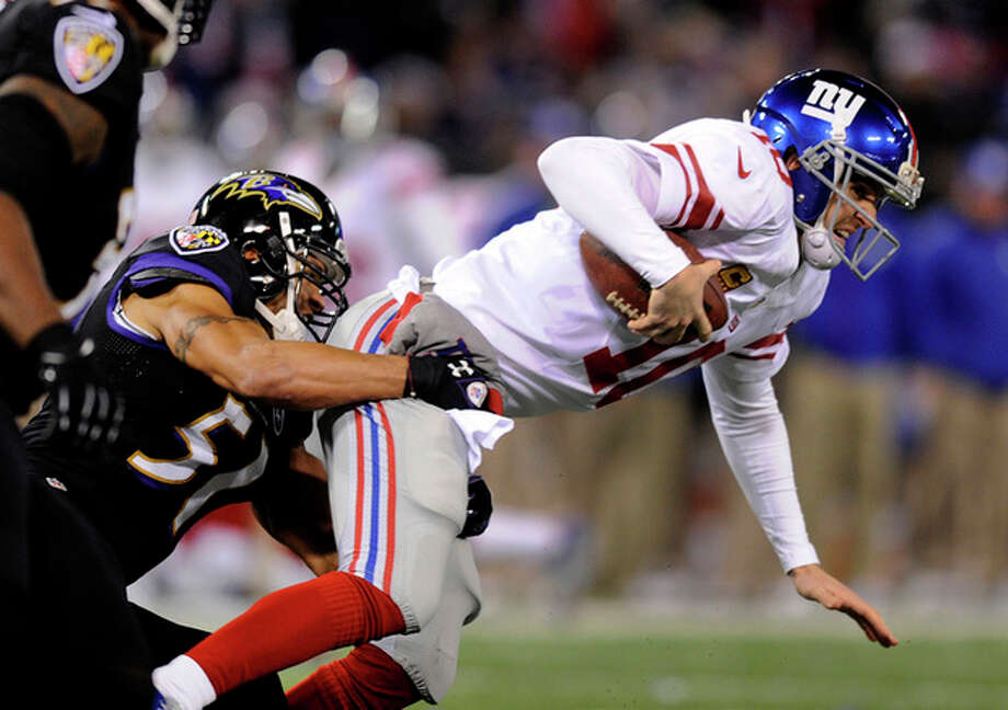 New York Giants quarterback Eli Manning, right, is sacked by Baltimore Ravens inside linebacker Brendon Ayanbadejo in the first half of an NFL football game in Baltimore, Sunday, Dec. 23, 2012. (AP Photo/Nick Wass) / FR67404 AP