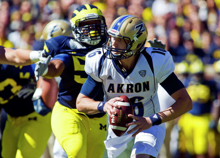 Michigan defensive tackle Jibreel Black (55) pressures Akron quarterback Kyle Pohl (16) in the first quarter of an NCAA college football game, Saturday, Sept. 14, 2013, in Ann Arbor, Mich. (AP Photo/Tony Ding) / FR143848 AP