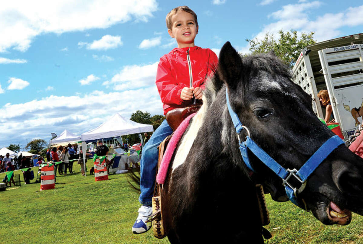 Blake Carlson rides a pony during the Live Green Connecticut! green-living and family festival Saturday at Taylor Farm Park. The two-day festival promotes living green with a focus on education, sustainability, caring for the environment and our natural resources.Hour photo / Erik Trautmann