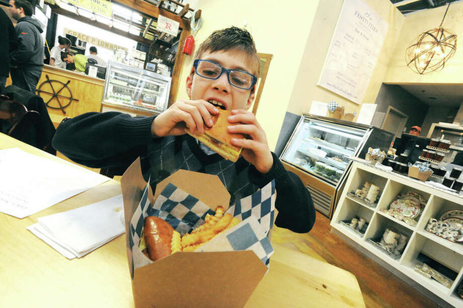Hour photos / Matthew VinciAlex D'Adamo, 9, sinks his teeth into a bacon, egg and cheese sandwich at Festivities eatery in the SoNo Marketplace on Sunday. Alex has his own food blog and writes reviews on his restaurant experiences.