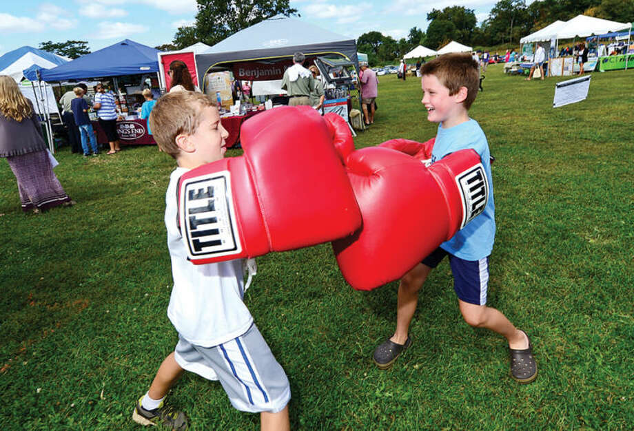 Garrett Volz and Jack Murray, both 8, try the Giant Boxing Gloves from Title Boxing Club during the Live Green Connecticut! green-living and family festival Saturday at Taylor Farm Park. The two-day festival promotes living green with a focus on education, sustainability, caring for the environment and our natural resources.Hour photo / Erik Trautmann