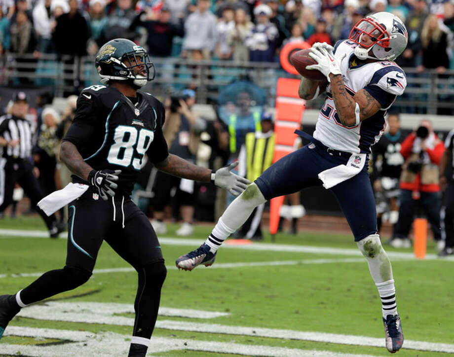 New England Patriots free safety Patrick Chung, right, intercepts a pass in front of Jacksonville Jaguars tight end Marcedes Lewis (89) as time expires in an NFL football game on Sunday, Dec. 23, 2012, in Jacksonville, Fla. New England won the game 23-16. (AP Photo/John Raoux) / AP