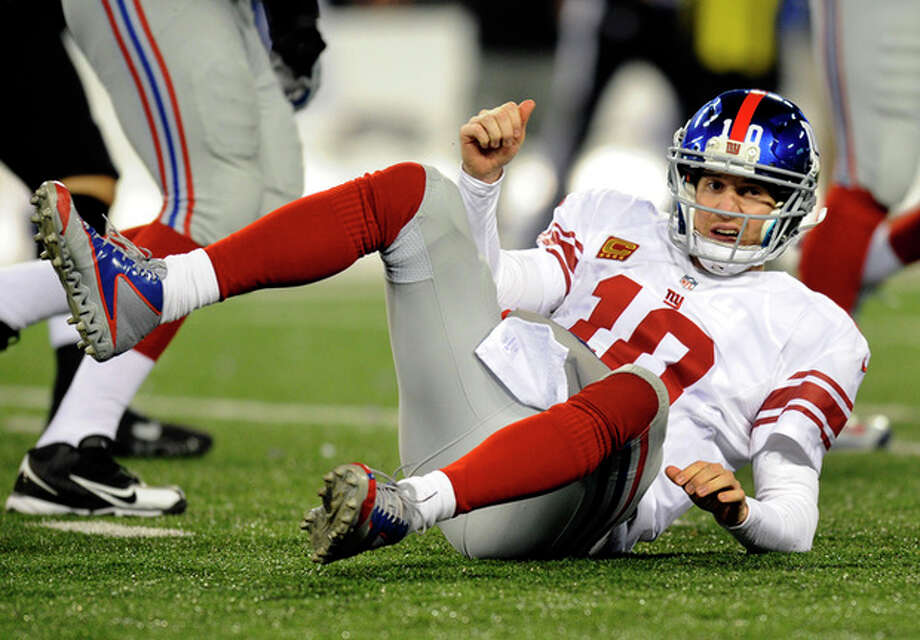 New York Giants quarterback Eli Manning gets up after being tackled by Baltimore Ravens defensive end Arthur Jones while throwing to a receiver in the first half of an NFL football game in Baltimore, Sunday, Dec. 23, 2012. (AP Photo/Nick Wass) / FR67404 AP