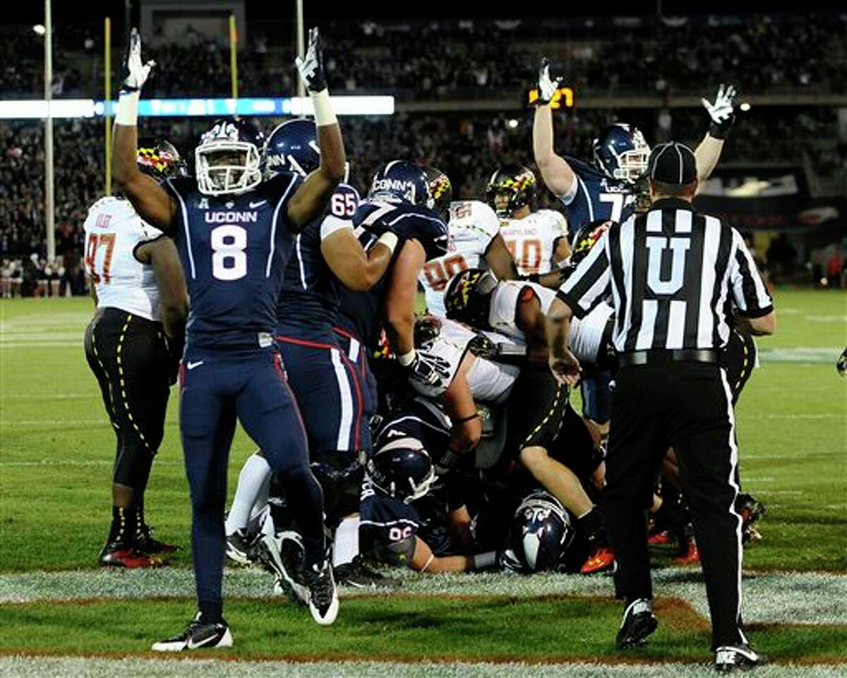 Connecticut wide receiver Shakim Phillips (8) celebrates a touchdown by running back Lyle McCombs, under the pile, during the first half of an NCAA college football game against Maryland at Rentschler Field, Saturday, Sept. 14, 2013, in East Hartford, Conn. (AP Photo/Jessica Hill)