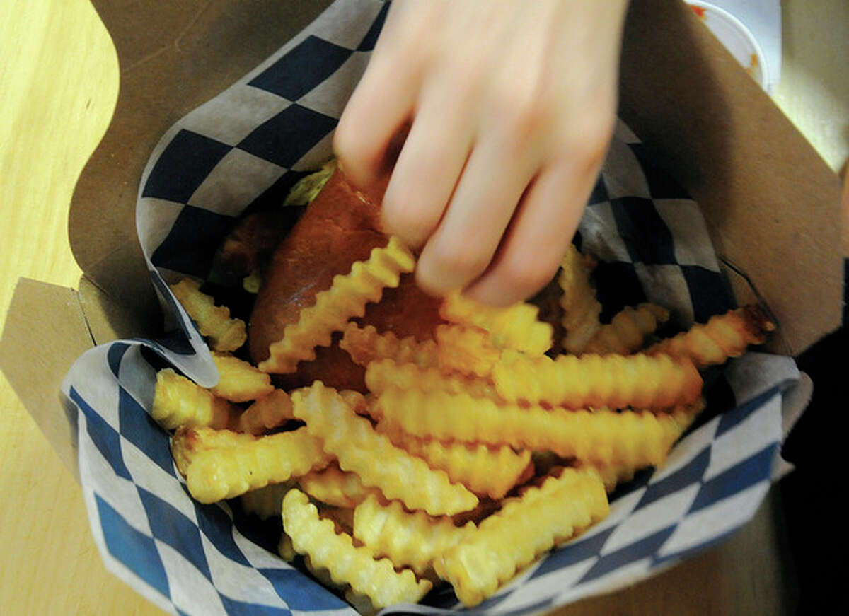 Alex D'Adamo reaches into his side order of a basket of french fries at Festivities on Sunday.