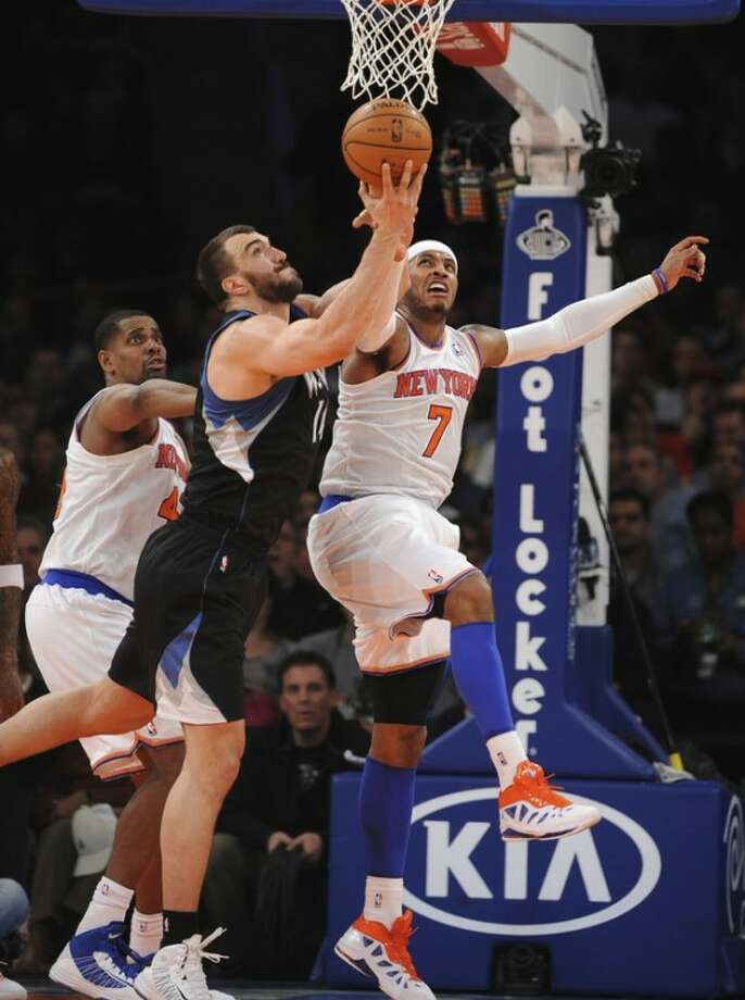 Minnesota Timberwolves' Nikola Pekovic (14) and New York Knicks' Carmelo Anthony (7) battle for a rebound in the first half of an NBA basketball game on Sunday, Dec., 23, 2012, at Madison Square Garden in New York. (AP Photo/Kathy Kmonicek)