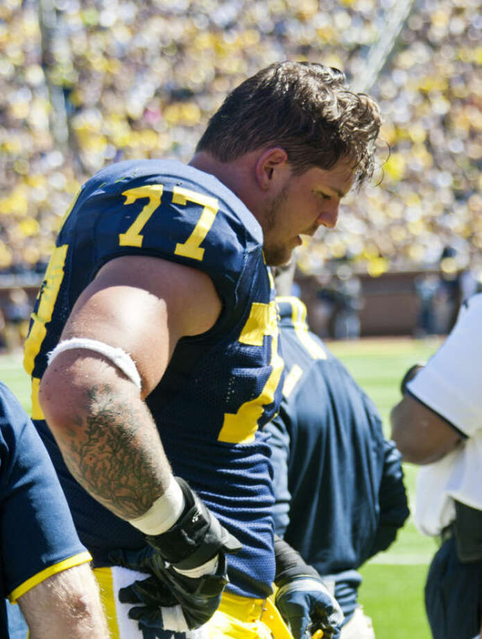 Michigan offensive lineman Taylor Lewan (77) walks to the bench after being helped off the field in the fourth quarter of an NCAA college football game against Akron in Ann Arbor, Mich., Saturday, Sept. 14, 2013. Michigan won 28-24. (AP Photo/Tony Ding)