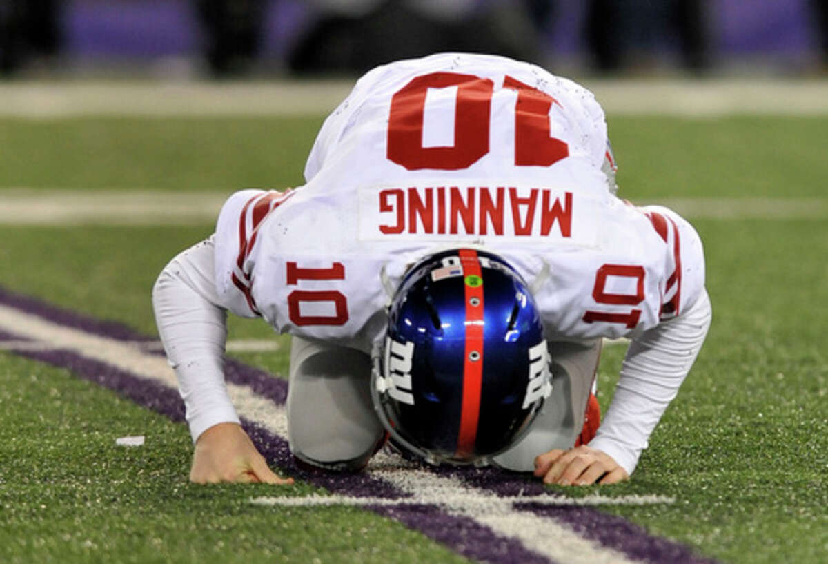 New York Giants quarterback Eli Manning gets up after being knocked over by Baltimore Ravens inside linebacker Brendon Ayanbadejo during the second half of an NFL football game in Baltimore, Sunday, Dec. 23, 2012. (AP Photo/Gail Burton)
