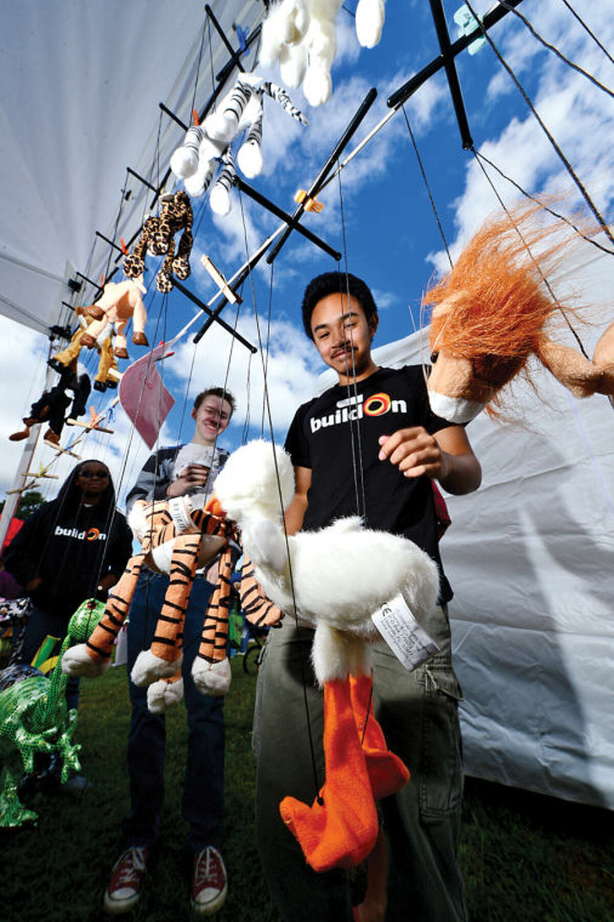 Dylan Ignacio looks at puppets from Jardin Delila during the Live Green Connecticut! green-living and family festival Saturday at Taylor Farm Park. The two-day festival promotes living green with a focus on education, sustainability, caring for the environment and our natural resources.Hour photo / Erik Trautmann