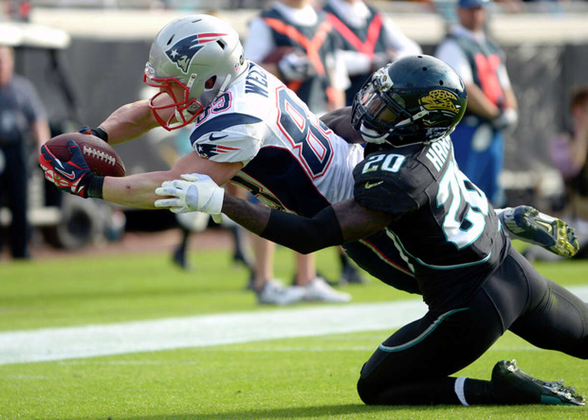 New England Patriots wide receiver Wes Welker (83) dives over the goal line past Jacksonville Jaguars cornerback Mike Harris (20) for a touchdown on a 2-yard pass play during the second half of an NFL football game on Sunday, Dec. 23, 2012, in Jacksonville, Fla. The Patriots won the game 23-16. (AP Photo/Phelan M. Ebenhack)
