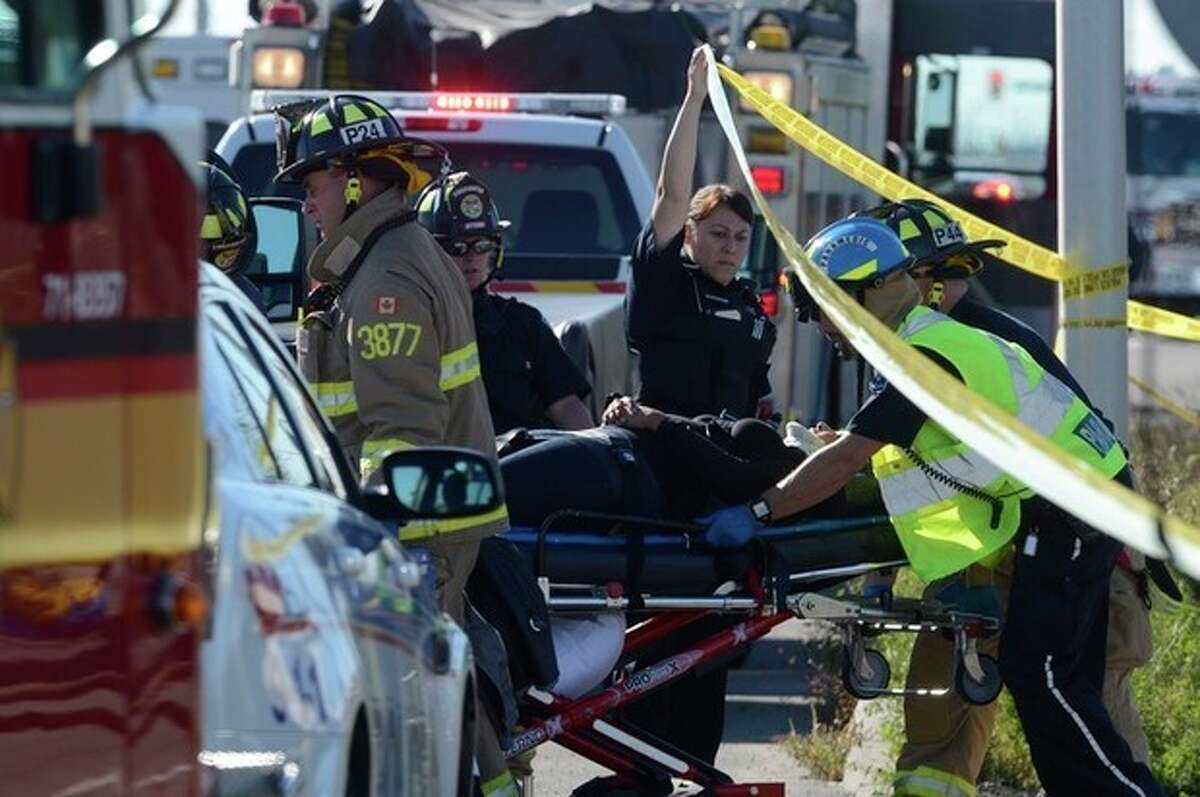 A passenger is taken to an ambulance following a Via Rail train and city bus collision in Ottawa's west end Wednesday, Sept. 18, 2013. Multiple people were killed when a passenger train collided with a city bus at a crossing at the peak of morning rush hour, police said Wednesday. Rescue crews swarmed over the wreckage. The injured from the bus who would walk were taken to a second bus nearby to be treated by paramedics. The train tracks in the area cross both a major city street and a transit line reserved for buses only. (AP Photo/The Canadian Press, Adrian Wyld)