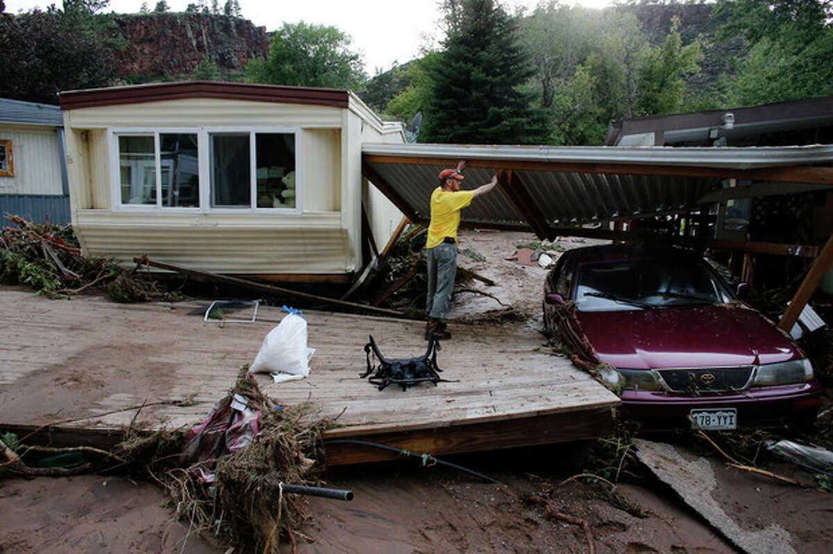 Local resident Ben Rodman helps a friend salvage her home after floods left homes and infrastructure in a shambles, in Lyons, Colo., Friday Sept. 13, 2013. Days of heavy rains and flash floods which washed out the town's bridges and destroyed the electrical and sanitation infrastructure have left many Lyons residents stranded with minimal access to help, and sectioned off the town into several pieces not reachable one to the other. (AP Photo/Brennan Linsley)