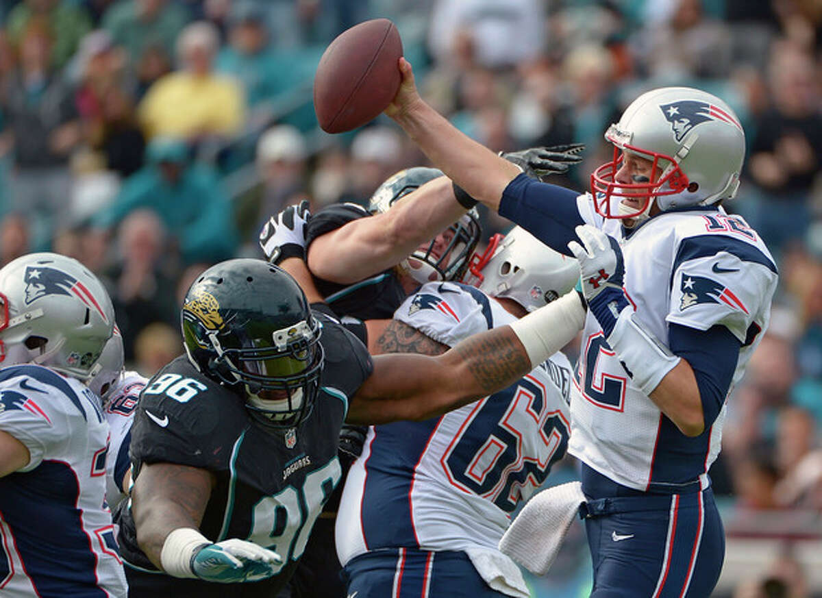 New England Patriots quarterback Tom Brady, right, makes a move to get away from Jacksonville Jaguars defensive tackle Terrance Knighton (96) during the first half of an NFL football game on Sunday, Dec. 23, 2012, in Jacksonville, Fla. The Patriots won the game 23-16. (AP Photo/Phelan M. Ebenhack)