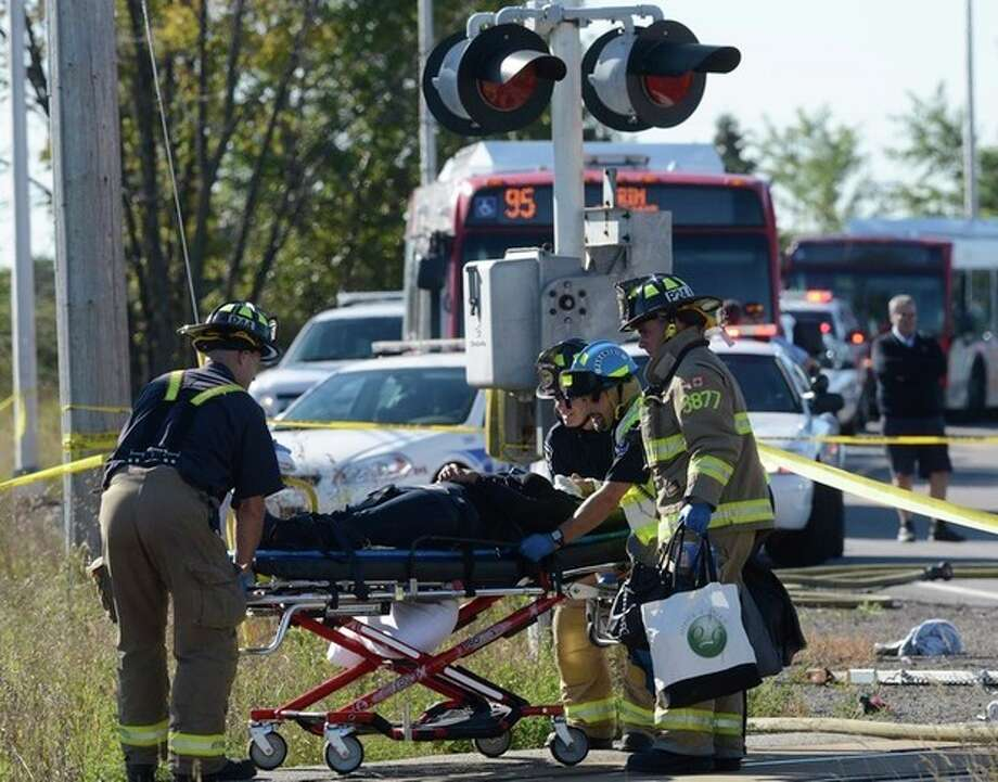A passenger is taken to an ambulance following a Via Rail train and city bus collision in Ottawa's west end Wednesday, Sept. 18, 2013. The collision at a level crossing took place at the peak of the morning commute. Passengers on the bus say they screamed at the driver to stop just before the crash, and witnesses on the ground said the bus plowed directly into the side of the passing, four-car train. (AP Photo/The Canadian Press, Adrian Wyld) / The Canadian Press