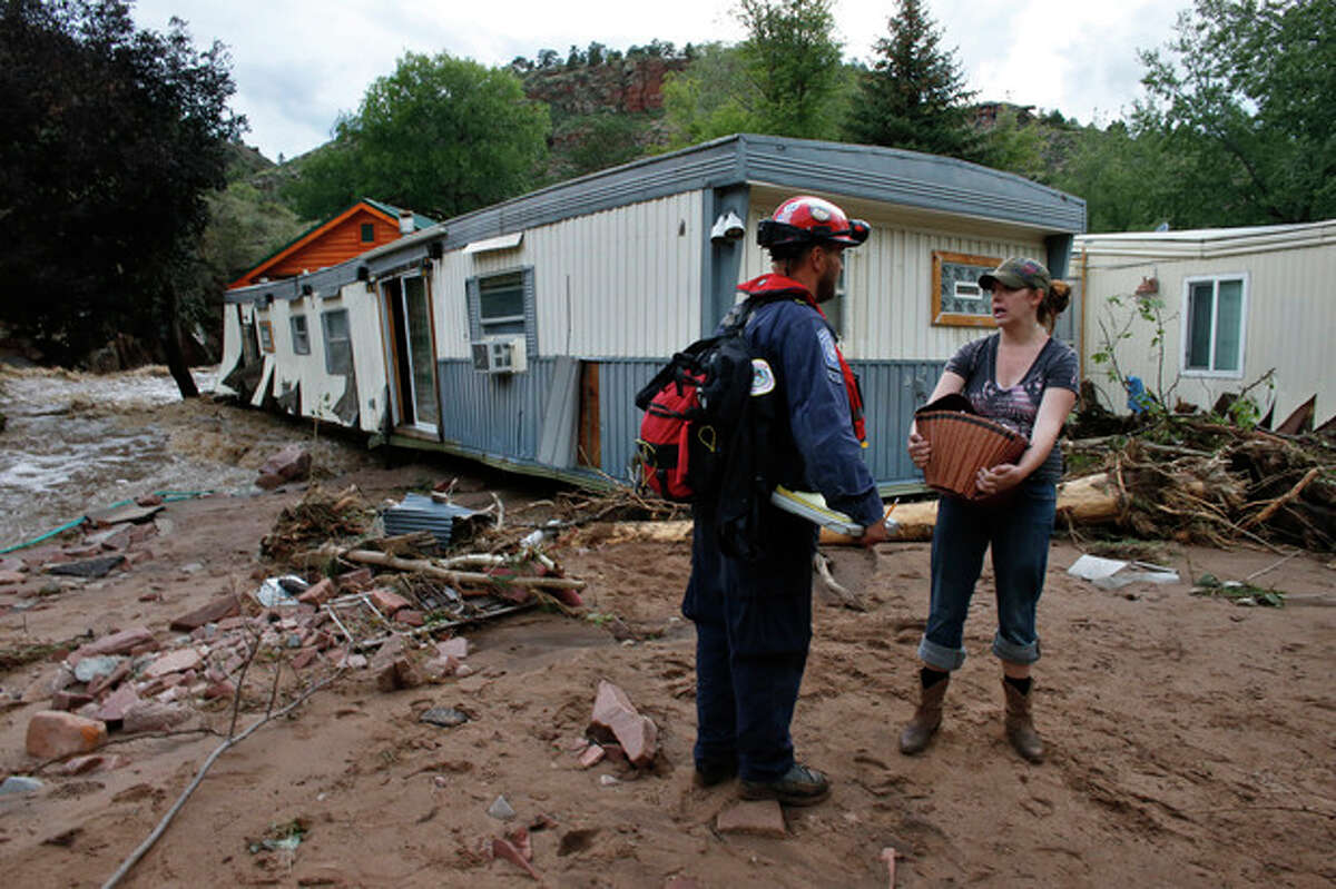 Local resident Holly Rob talks with an emergency responder as she recovers belongings from her home which was nearly swept away in flooding, in Lyons, Colo., Friday Sept. 13, 2013. Days of heavy rains and flash floods which washed out the town's bridges and destroyed the electrical and sanitation infrastructure have left many Lyons residents stranded with minimal access to help, and sectioned off the town into several pieces not reachable one to the other. (AP Photo/Brennan Linsley)