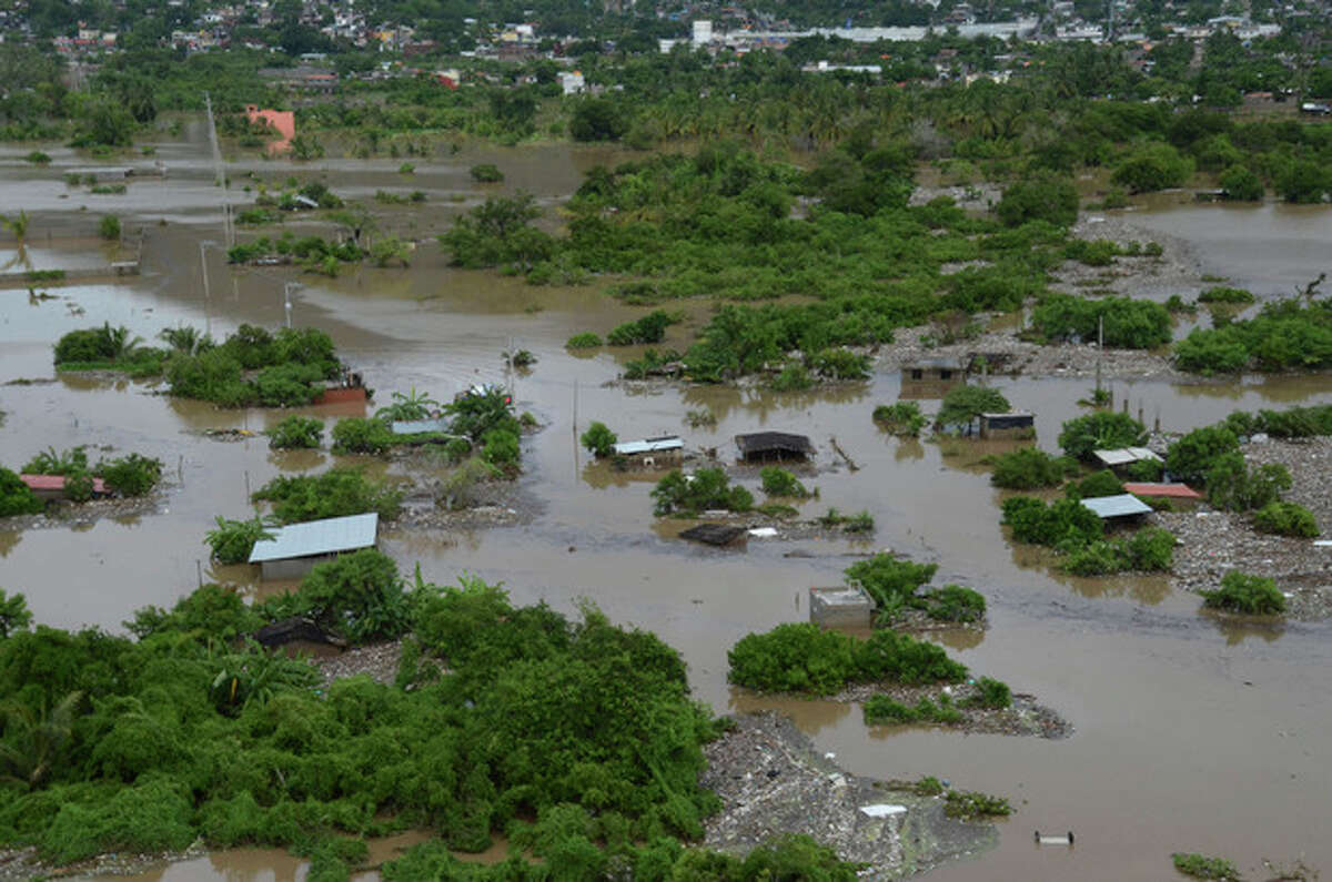 A low income neighborhood is covered by floodwaters caused by Tropical Storm Manuel in Acapulco, Mexico, Tuesday, Sept. 17, 2013. The death toll rose to 47 Tuesday from the unusual one-two punch of a tropical storm and a hurricane hitting Mexico at nearly the same time. Authorities scrambled to get help into, and stranded tourists out of, the cutoff resort city of Acapulco. (AP Photo/Bernandino Hernandez)