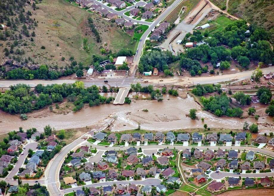 A residential neighborhood and a connecting road in Lyons, Colo., are cut in two by flood waters as flooding continues to devastate the Front Range and thousands are forced to evacuate with an unconfirmed number of structures destroyed Friday, Sept. 13, 2013. (AP Photo/John Wark) / AP