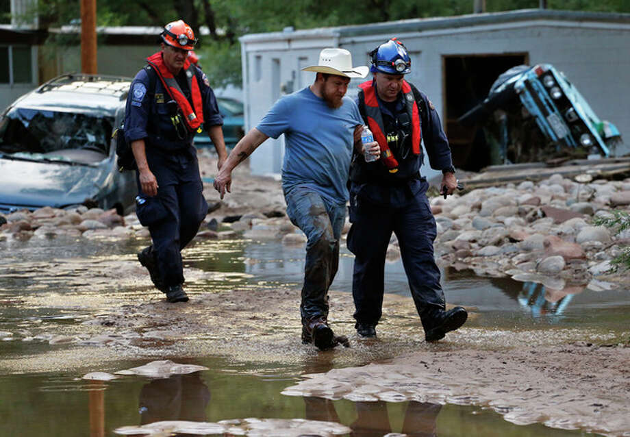 Suffering from dehydration, local resident Fred Rob gets help from emergency responders as he leaves his neighborhood, after floods left homes and infrastructure in a shambles, in Lyons, Colo., Friday Sept. 13, 2013. Days of heavy rains and flash floods which washed out the town's bridges and destroyed the electrical and sanitation infrastructure have left many Lyons residents stranded with minimal access to help, and sectioned off the town into several pieces not reachable one to the other. (AP Photo/Brennan Linsley) / AP