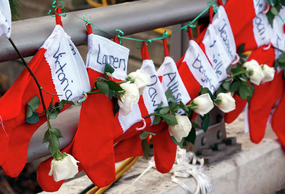 FILE - In this Wednesday, Dec. 19, 2012 file photo, Christmas stockings with the names of shooting victims hang from railing near a makeshift memorial near the town Christmas tree in the Sandy Hook village of Newtown, Conn. In the wake of the shooting, the grieving town is trying to find meaning in Christmas. (AP Photo/Julio Cortez, File) / AP