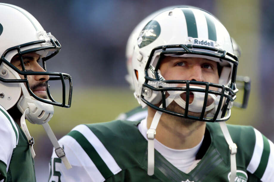 New York Jets quarterbacks Mark Sanchez, left, and Tim Tebow stand next to each other during the second half of an NFL football game against the San Diego Chargers, Sunday, Dec. 23, 2012, in East Rutherford, N.J. (AP Photo/Kathy Willens) / AP