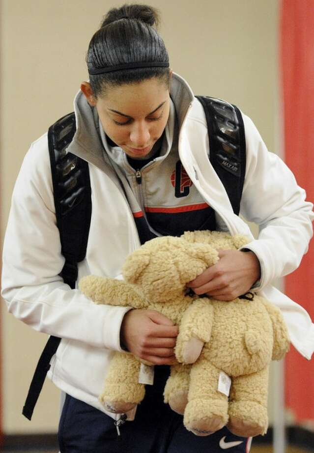 Connecticut's Bria Hartley leaves a news conference holding two teddy bears given to her by children from the Newtown Youth Basketball Association after an NCAA women's college basketball game against Hartford at the University of Hartford in West Hartford, Conn., Saturday, Dec. 22, 2012. (AP Photo/Jessica Hill)