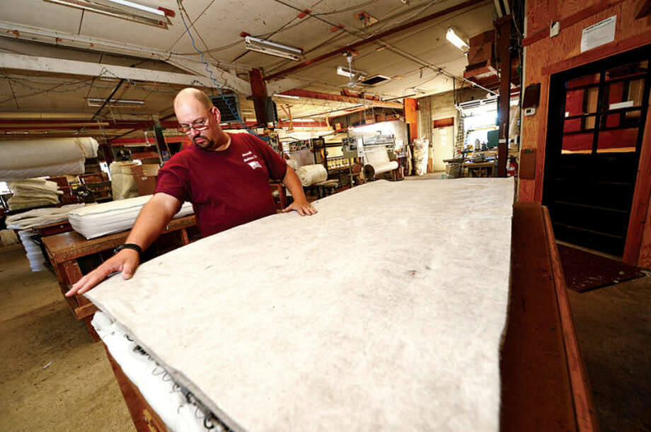 Mark Sastram assembles mattresses at Norwalk Mattress Co. on West Cedar St. in Norwalk. Norwalk Mattress has been manufacturing mattresses in Norwalk since 1918. Hour photo / Erik Trautmann