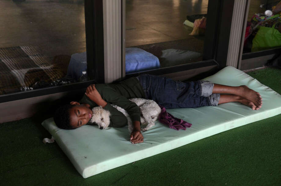A child lies with his dog at a shelter set up for people affected by Tropical Storm Manuel in the city of Acapulco, Mexico, Tuesday Sept. 17, 2013. The death toll rose to 47 Tuesday from the unusual one-two punch of a tropical storm and a hurricane hitting Mexico at nearly the same time. Authorities scrambled to get help into, and stranded tourists out of, the cutoff resort city. (AP Photo/Bernandino Hernandez) / AP