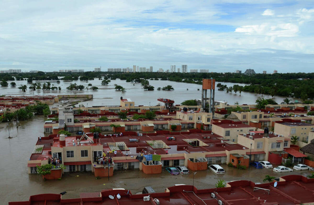 People stand on the rooftop of a home in a flooded neighborhood after Tropical Storm Manuel pounded Acapulco, Mexico, Tuesday, Sept. 17, 2013. The death toll rose to 47 Tuesday from the unusual one-two punch of a tropical storm and a hurricane, hitting Mexico at nearly the same time. Authorities scrambled to get help into, and stranded tourists out of, the cutoff resort city. (AP Photo/Bernandino Hernandez)