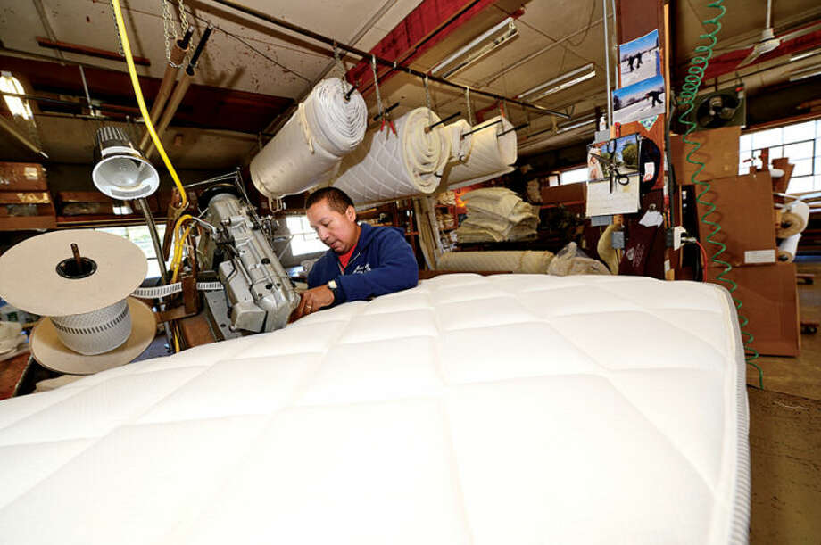 Tony Maye builds mattresses at Norwalk Mattress Co. on West Cedar St. in Norwalk. Norwalk Mattress has been manufacturing mattresses in Norwalk since 1918. Hour photo / Erik Trautmann