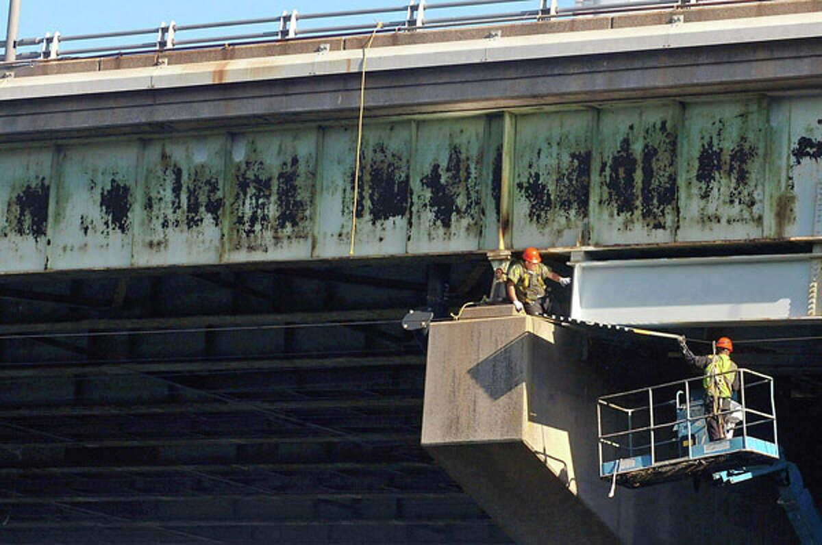 Workers begin with bridge maintenance and repair underneath the Yankee Doodle Bridge in Norwalk Thursday. Hour photo / Erik Trautmann
