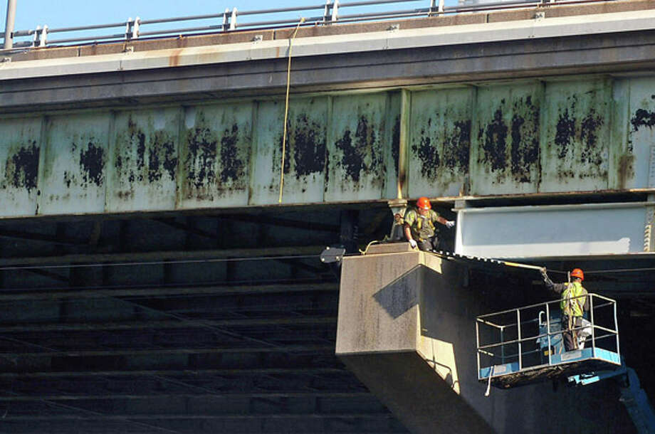 Workers begin with bridge maintenance and repair underneath the Yankee Doodle Bridge in Norwalk Thursday. Hour photo / Erik Trautmann / (C)2012, The Hour Newspapers, all rights reserved