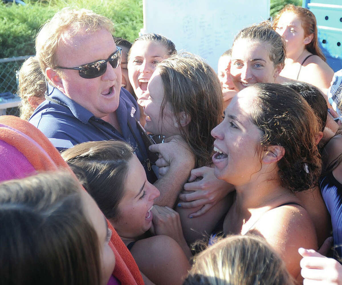 Hour photo/John Nash Wilton girls swimming coach Todd Stevens, top left, is mobbed by his team after the official score was read following the 100th dual meet victory of his career. Wilton bested Trumbull 99-87 to reach the milestone.