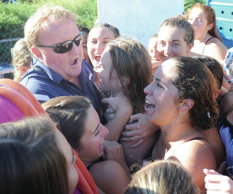 Hour photo/John NashWilton girls swimming coach Todd Stevens, top left, is mobbed by his team after the official score was read following the 100th dual meet victory of his career. Wilton bested Trumbull 99-87 to reach the milestone.
