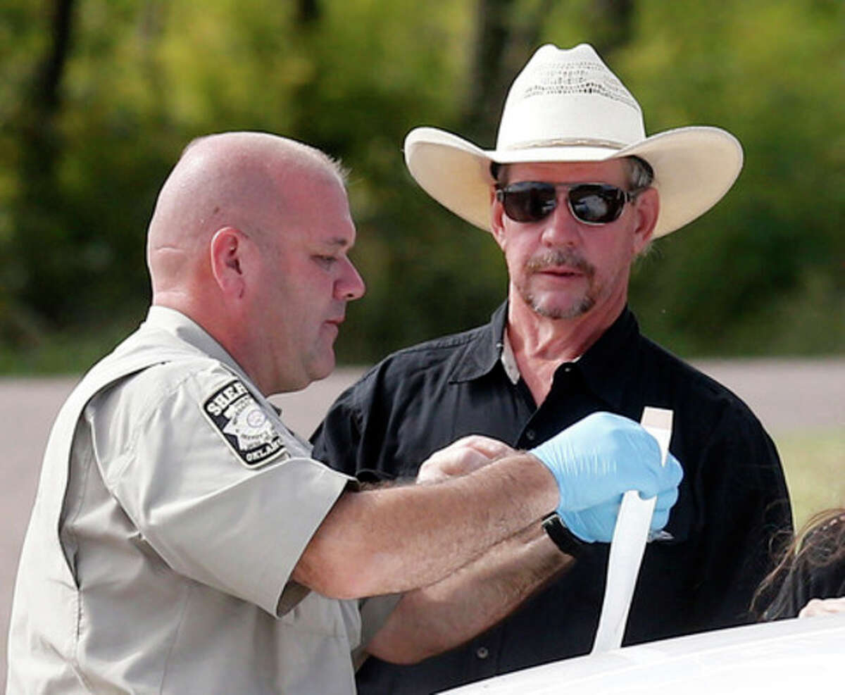 Tim Porter, right, talks with Beckham County Sheriff's Deputy J. Kessel, left, after giving a DNA sample at the scene where two cars were found in Foss Lake, in Foss, Okla., Wednesday, Sept. 18, 2013. Porter says he believes his grandfather's remains may be in one of the cars. The Oklahoma State Medical Examiner?'s Office says authorities have recovered skeletal remains of multiple bodies in the Oklahoma lake where the cars were recovered. (AP Photo/Sue Ogrocki)