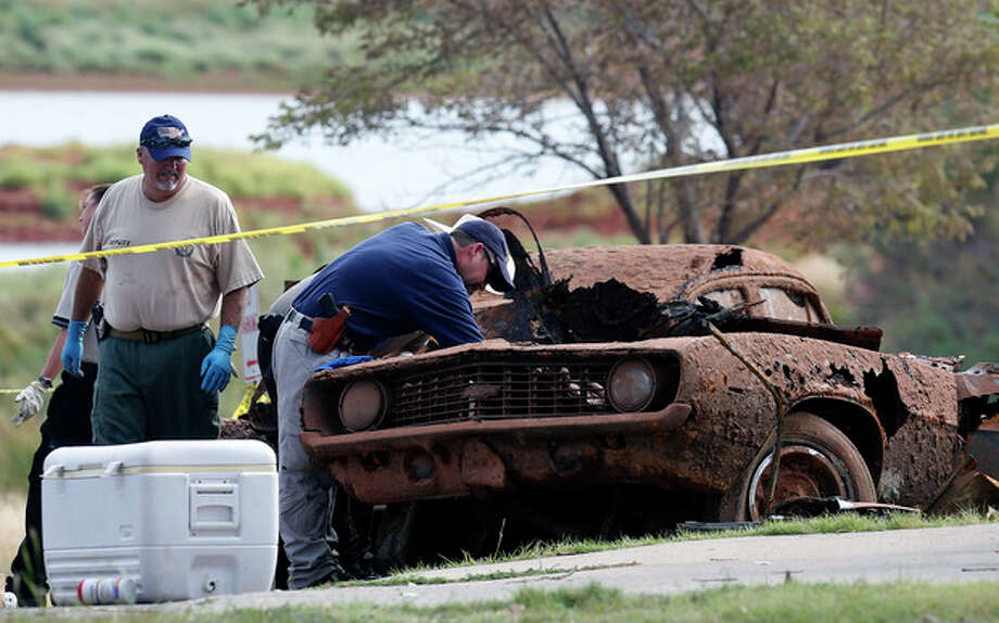 Law enforcement officials from multiple agencies examine the two cars pulled from Foss Lake, in Foss, Okla., Wednesday, Sept. 18, 2013. The Oklahoma State Medical Examiner's Office says authorities have recovered skeletal remains of multiple bodies in the Oklahoma lake where the cars were recovered. (AP Photo/Sue Ogrocki) / AP