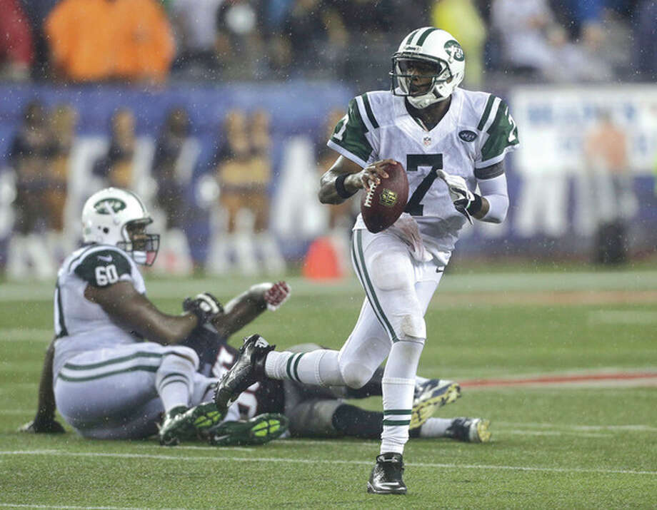 AP photoNew York Jets quarterback Geno Smith (7) scrambles against the New England Patriots during a Sept. 12 game in Foxborough, Mass. Smith will square off against another rookie quarterback, E.J. Manuel, when the Jets face the Buffalo Bills Sunday. / AP