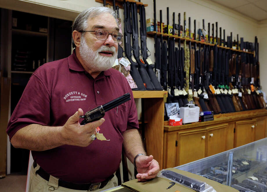 In this photo taken Wednesday, Dec. 19, 2012, gun store owner Dave Burdett talks about gun rights as he displays a hand gun in his store in College Station, Texas. Burdett, who owns an outdoors and adventure shop across the street from the sprawling Texas A&M University campus in College Station, says his affinity for guns is rooted in history, not sport. (AP Photo/Pat Sullivan) / AP