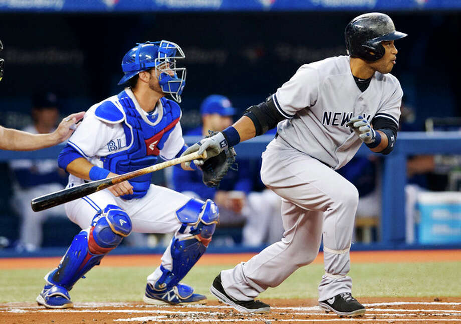 New York Yankees' Robinson Cano follows through on a base hit in front of Toronto Blue Jays catcher J.P. Arencibia, right, during the first inning of MLB American League baseball action in Toronto Wednesday, Sept. 18, 2013. (AP Photo/The Canadian Press, Mark Blinch) / Canadian Press