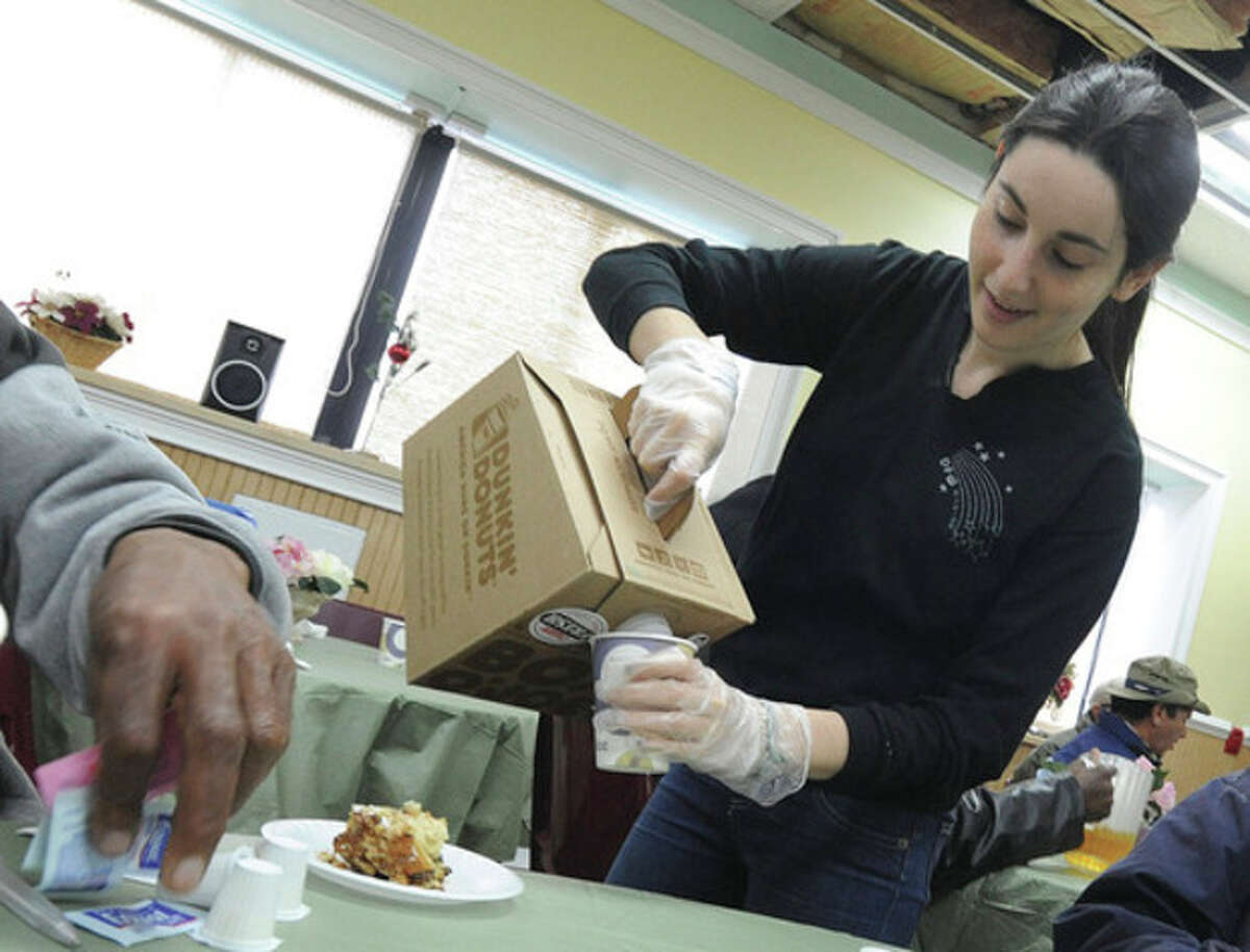 Hour photo / Matthew Vinci Danielle Kleinman volunteers to serve food and other refreshments on Christmas Day at the Open Door Shelter in South Norwalk.