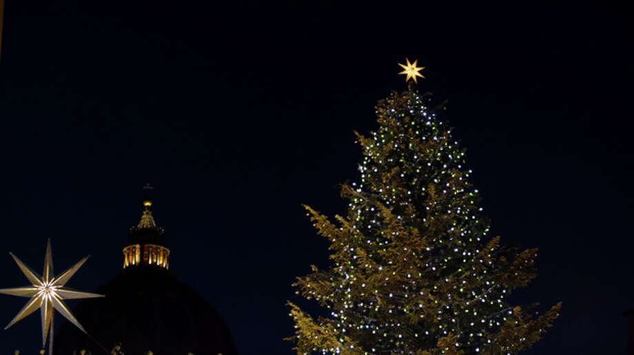 The dome of St. Peter's Basilica, center, is framed by a Christmas tree at the Vatican Monday, Dec. 24, 2012. Pope Benedict XVI has lit a Christmas peace candle set on the windowsill of his private studio overlooking square. Pilgrims, tourists and Romans gathered below in St. Peter's Square for the inauguration Monday evening of a Nativity scene and cheered when the flame was lit. Later, he will appear in St. Peter's Basilica to lead Christmas Eve Mass. (AP Photo/Gregorio Borgia) / AP