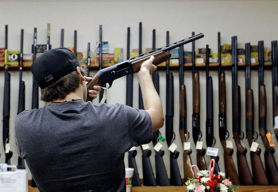 In this photo taken Wednesday, Dec. 19, 2012, a customer checks out a shotgun at Burdett & Son Outdoor Adventure Shop in College Station, Texas. More civilians are armed in the U.S. than anywhere else in the world, with Yemen coming in a distant second, according to the Small Arms Survey in Geneva. (AP Photo/Pat Sullivan) / AP