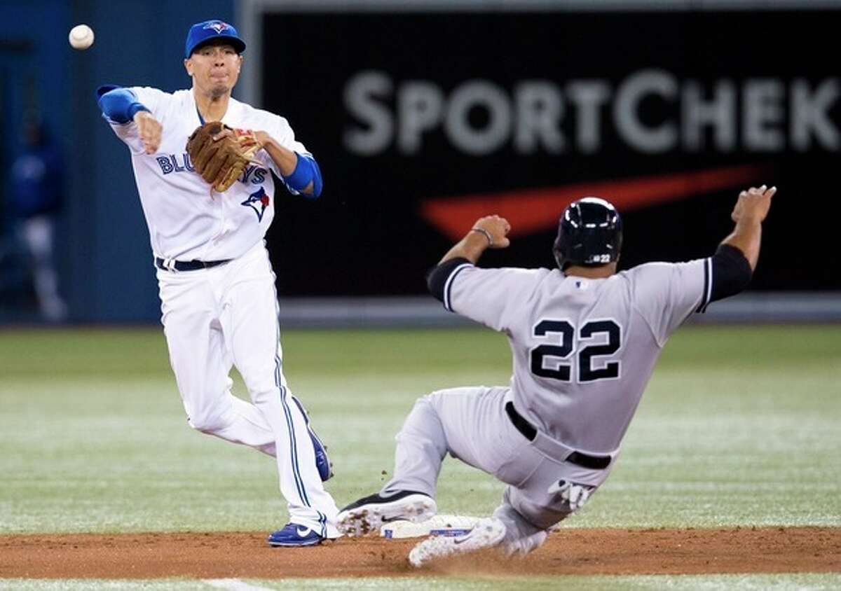 Toronto Blue Jays' Ryan Goins turns a double play over New York Yankees' Vernon Wells, right, during the fourth inning of MLB American League baseball action in Toronto Wednesday, Sept. 18, 2013. (AP Photo/The Canadian Press, Mark Blinch)