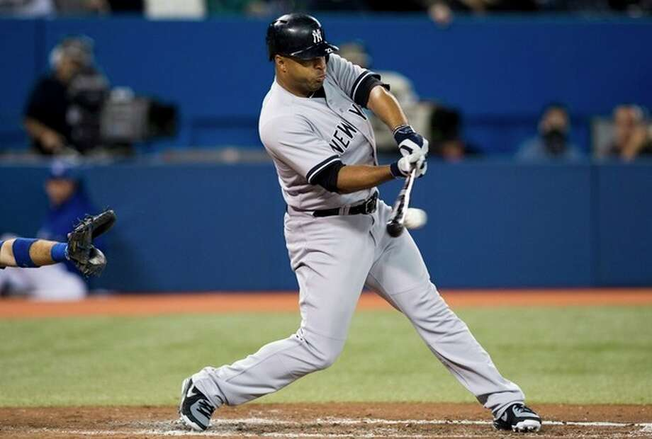 New York Yankees' Vernon Wells hits a single against the Toronto Blue Jays during the third inning of MLB American League baseball action in Toronto Wednesday, Sept. 18, 2013. (AP Photo/The Canadian Press, Mark Blinch) / Canadian Press