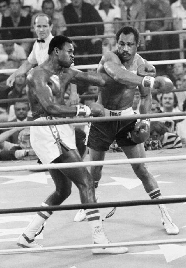 FILE - In this June 9, 1978, file photo, Ken Norton, right, follows through with his right as Larry Holmes misses during an early round of their heavyweight championship fight in Las Vegas. Norton, a former heavyweight champion, has died, his son said, Wednesday, Sept. 18, 2013. He was 70. (AP Photo/File_