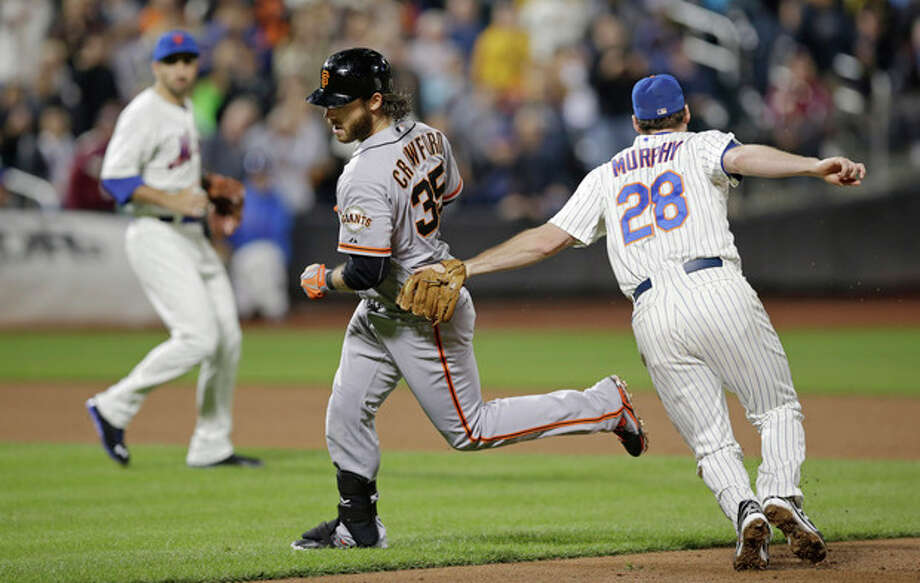 New York Mets second baseman Daniel Murphy (28) picks off San Francisco Giants' Brandon Crawford (35) after Crawford was caught in a rundown advancing on the throw on his fifth-inning RBI-single in a baseball game on Wednesday, Sept. 18, 2013, in New York. (AP Photo/Kathy Willens) / AP