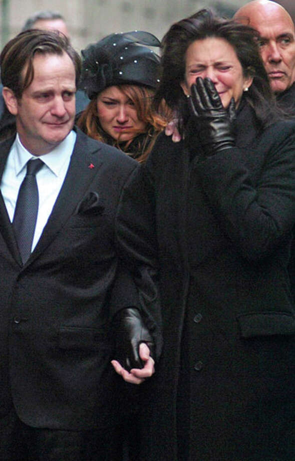 Matthew Badger, left, and Madonna Badger, the parents of three children that were killed in a fire on Christmas Day, react as their coffins are carried into a church during the funeral in Manhatten . Hour photo / Erik Trautmann / (C)2011, The Hour Newspapers, all rights reserved