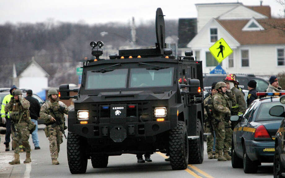 A Monroe County Sheriff's Department armored truck drops off residents who were evacuated from the neighborhood, Monday, Dec. 24, 2012 in Webster, New York. A former convict set a house and car ablaze in his lakeside New York state neighborhood to lure firefighters then opened fire on them, killing two and engaging police in a shootout before killing himself while several homes burned. Authorities used an armored vehicle to evacuate the area. (AP Photo/Democrat & Chronicle, Max Schulte) / Democrat and Chronicle Gannett Rochester