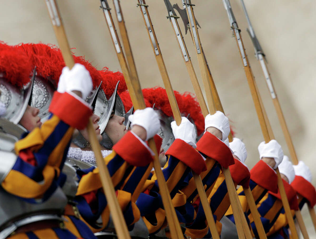 """Vatican Swiss guards stand attention before Pope Benedict XVI delivers his """"Urbi et Orbi"""" (to the City and to the World) in St. Peter's Square, at the Vatican, Tuesday, Dec. 25, 2012. Pope Benedict XVI has wished Christmas peace to the world, decrying the slaughter of the """"defenseless"""" in Syria and urging Israelis and Palestinians to find the courage to negotiate. Delivering the Vatican's traditional Christmas day message from the central balcony of St. Peter's Basilica, a weary-looking and hoarse-sounding Benedict on Tuesday also encouraged Arab spring nations, especially Egypt, to build just and respectful societies. (AP Photo/Gregorio Borgia)"""