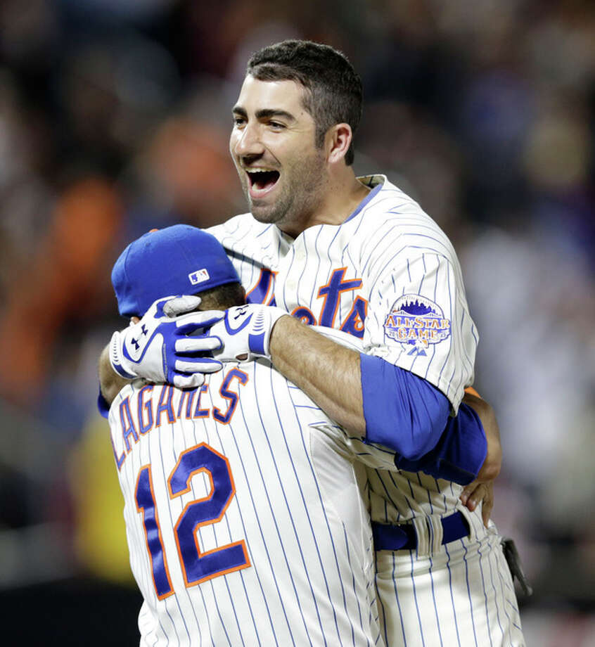 New York Mets Josh Satin leaps into the arms of teammate Juan Lagares after hitting a ninth-inning walkoff two-run single to lift the Mets to a 5-4 victory over the San Francisco Giants in a baseball game on Wednesday, Sept. 18, 2013, in New York. (AP Photo/Kathy Willens) / AP